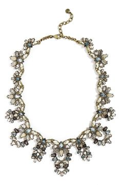 A modern take on a vintage design, this antiqued goldtone collar necklace makes a statement with crystal cutout pendants in opalescent hues.