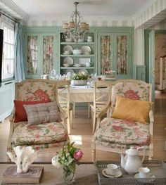 Snug cottage sitting room/dining area. Love the built-in cabinets with fabric and the chintz on the chairs. A great look for a small space.