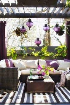 El patio es colorido y tiene muchas plantas, flores, y una sofa.