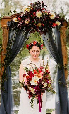 Bride with a wildflower bouquet in the woods with a vintage rustic arch