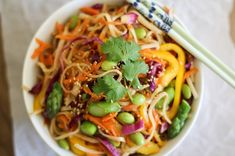 Spring Vegetable Pad Thai Recipe with pad thai brown rice noodles, yellow bell pepper, shredded carrots, red cabbage, frozen shelled edamame, asparagus, liquid aminos, sesame oil, peanut butter, peanut butter, sesame seeds, chopped fresh cilantro, soy sauce