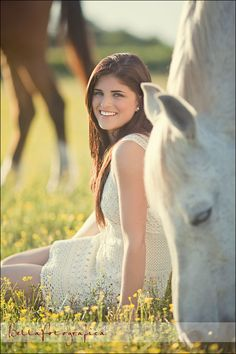 pretty girl sitting in field with horses