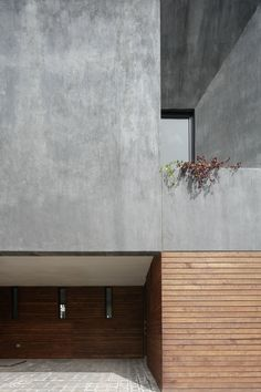 The home's exterior is covered in natural wood around the bottom and black stucco at the top, with minimal windows facing the street to create privacy.