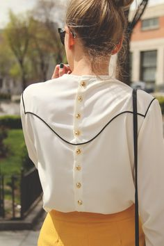 Long sleeve back-button-down blouse with black western piping. Paired with a mustard leather skirt and black cat-eyed sunglasses.