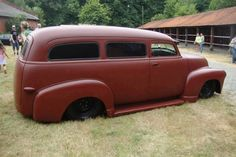 satin burgundy painted chopped and slammed Chevy Chevrolet Advanced Design 1947 1948 1949 1950 1951 Suburban sitting black walls and black steel wheels. The builder even shaved the rear barn door hinges and swapped in late model flush door handles.