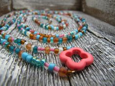 A fun multicolored coral clover wrap around necklace, best worn wrapped around neck two times. NECKLACE DETAILS: - Coral clover pendant dimensions: x - Bead colors: multicolored - Option 1 necklace length: - Option 2 necklace length: Wrap Around, Turquoise Bracelet, Coral, Beaded Bracelets, Pendant Necklace, Trending Outfits, Unique Jewelry, Handmade Gifts, Etsy