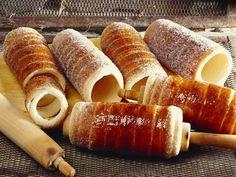 Baumkuchen auf ungarische Art 100 ml lauwarme Milch 1 Päckchen Vanillezucker 5 EL Zucker 500 g Mehl 1 Würfel Hefe 42 g Salz 2 Eier 1 Msp. Zitronenschale Mehl für die Arbeitsfläche 2 EL gemahlene Haselnüsse 100 g zerlassene Butter