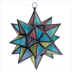 """An intricate three-dimensional star is crafted in colorful glass and dark metal to create a dramatic hanging candle lantern for indoor display or in garden or patio. Stained glass hanging star lantern measures 11"""" x 11"""" x 14"""" high. Metal frame, glass panels."""