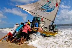 Jangadeiros (Ceara, Brazil) Jan Sochor Photography Jangadeiros move the boat towards the sea using wooden logs. Jangada has an unfixed keel