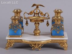 Late 19th century, with a gilt and marble stand, central element which is decorated with an eagle and bell flowers and four opaline blue scent bottles. Each lid decorated with classical structures.