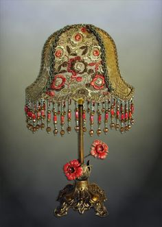 Sweet little table lamp from the 1920s. Covered in gold metallic lace and colorful embroidered net in pale greens and persimmon. Hand beaded glass fringe.