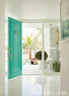 A bold turquoise door makes for a cheerful entrance in this Palm Springs showhouse. - Photo: Karyn Millet
