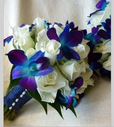 Blue Orchids and White roses!  Omg yes!! Teal, purple and white are def gonna be my wedding colours... they are my fave after all.