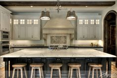 The island features white Calcutta Carrera marble atop rich ebony cabinetry while the perimeter has black Zimbabwe granite and creamy white cabinets. The back splash combines old French concrete tiles from Chateau Domingue with a contemporary field tile. Such a dreamy kitchen