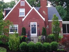 Landscaping that accents this two-story house and frames a front deck also reduces lawn mowing on this steep yard.