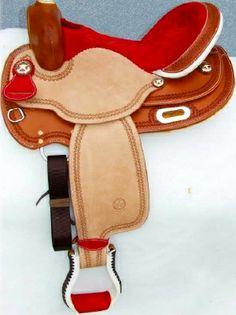 Sella  GARLAND  art.  GD302DT  nel  colore cognac  con  seggio  in  camoscio  rosso  e  seat  jokey  e  fender  in  cuoio  rovesciato. Pomo,  paletta  e  staffe  in  rawhide. Lavorazione  double  tooling.