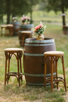 Wine barrel cocktail table with wooden bar stools and a gold painted vase of flowers for rustic wedding | Cavanagh Photography