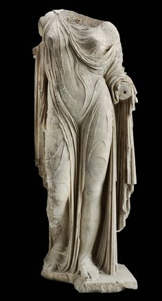 The plinth is broken away in front of the right foot. The right arm and right shoulder were made separately and attached with a large pin or clamp. The drapery is chipped. The surfaces are incrusted and have a yellowish patina.Statue of Aphrodite or a Roman lady Roman Imperial Period about mid-1st century A.D.