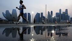 A man jogs along Marina Bay, with the city skyline of the central business district in the background, in Singapore April 6, 2015. Reuters