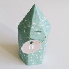 une boîte bleue avec des étoiles, en papier découpé et plié, pour fabriquer un paquet cadeau.