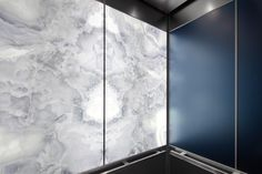LEVELe-106 Elevator Interior with LightPlane Panels in ViviStone Pearl Onyx glass, Pearlex finish, illuminated; panels in ViviChrome Chromis glass with Slate Blue interlayer and Pearlex finish, Stainless Steel, Seastone finish; Quadrant handrails at 1100 Louisiana Street, Houston, Texas