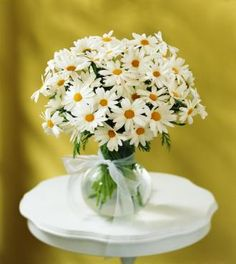 White daisy table arrangements but with a Tiffany blue bow around them instead
