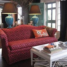 Lisa Sherry  camelback sofa, sofa table, vase of branches, foo dogs, white foo dogs, glossy turquoise table lamps, turquoise urn lamps, brown shades, black walls, black painted walls, green blue front door, white tray coffee table, white coffee table, black and white hide rug,chandelier, chinoisserie pillow, La Florentina fabric,