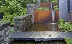 corten retaining wall | Steel Water Feature, long stone slab over contemporary pond