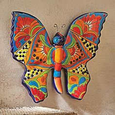 Talavera-style Butterfly Wall Art--Talavera pottery combines centuries of Moorish tradition, Spanish technique, and Mexican skill. Artisans hand-mold this ceramic butterfly, which is allowed to dry in the sun before being painted with a bright white glaze. Then, its wings are decorated using a traditional color palette of blue, green, yellow, red, brown, and black glaze. The result is a vibrant sculpture made in the talavera style by a family-run studio in Dolores Hidalgo, Mexico.