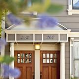 Small window pane inserts in these wooden duplex doors bring a touch of elegance to a charming curb appeal design.