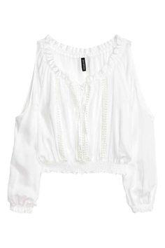 Blusa cut-out: Blusa corta en viscosa vaporosa con ribetes de encaje, cuello elástico con tiras de anudar delante, mangas largas con secciones cut-out, y puños y bajo fruncidos.