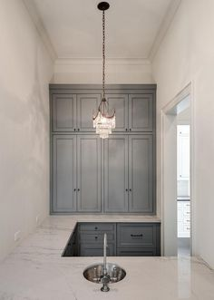 Small blue gray wet bar features an eye-catching small crystal chandelier hung over a round hammered metal sink accented with an antique satin nickel faucet fix in a u-shaped white quartzite countertop complementing blue gray cabinets fitted with oil rubbed bronze hardware.