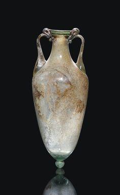 A ROMAN GREEN GLASS AMPHORA CIRCA 1ST-2ND CENTURY A.D.