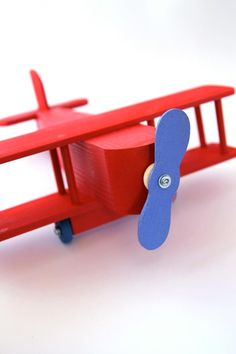 Red wooden airplane with a blue propeller, made from pine wood.