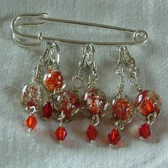 Crackled red stitch markers made with glass beads on a kilt pin brooch.    http://folksy.com/shops/kingfishergems