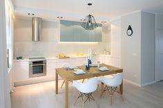 W otwartej strefie dziennej jadalnia stanowi subtelną granicę między kuchnią a salonem. Ustawione przy drewnianym stole białe krzesła podkreślają jej nowoczesny charakter. Projekt Anna Maria Sokołowska. Fot. Bartosz Jarosz.