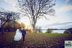 The bride & groom walk towards the Lake at Tulfarris. Beautiful autumn leaves & colours. Weddings at Tulfarris Hotel & Golf Resort. Photographed by Couple Photography.