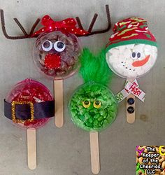 Christmas Treat Pops  MATERIALS USED:   Plastic Fill- able Ornaments (I would recommend checking for food safe ones) find some like the ones I used –> HERE Green M&M's Red M&M's Jumbo Craft Sticks HERE Construction paper Hot glue and glue gun scissors Chenille stems- brown & Gold Red pom pom Dollar store child size sock Green Feathers Wiggle Eyes Ribbon (Christmas and black) Small Buttons black sharpie Marshmallows and Malt balls  DIRECTIONS: Start off by filling half of your (cleaned food…