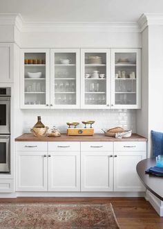 Glass front white cabinets butcher block counter, modern white kitchen with breakfast table, built-in banquette, white shaker cabinets White Shaker Kitchen Cabinets, Glass Kitchen Cabinets, Glass Front Cabinets, Modern Kitchen White Cabinets, Diy Cupboards, Farmhouse Cabinets, Glass Cabinet Doors, Grey Cabinets, Cabinet Hardware