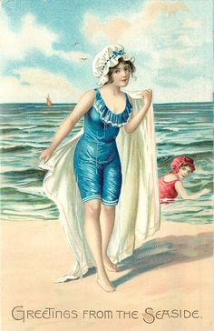woman in blue suit stands with towel over shoulders, woman in red suit in sea to right