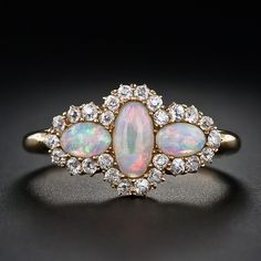 This colorful and darling antique opal ring, made in jolly ol' England, circa 1890, features three entrancing oval opals which exhibit a full range of colors: fiery red, orange and yellow against tranquil pastel blues and greens. The three beautiful opals are outlined in tiny twinkling old mine diamonds. 18 karat yellow gold, British hallmarks.