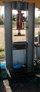 Homemade press constructed from channel steel and powered by a treadle-actuated hydraulic cylinder.