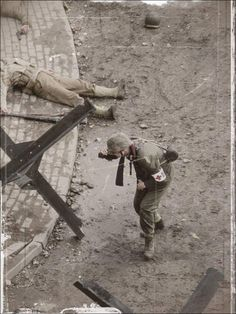 German medic seeking cover behind an anti-tank obstacle.  You can see two dead American soldiers near him.  You can make out the M1911 .45 caliber handgun in the soldier's hand.