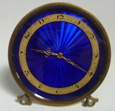 A 1930's Art Deco circular gild bedside clock, Swiss movement with blue enamelled dial and gilt chapter ring supported on an easel base #artdeco #ukauctioneers