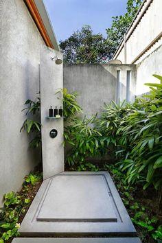 Une douche extérieure dans un coin isolé naturellement décoré par les plantes vertes exotiques
