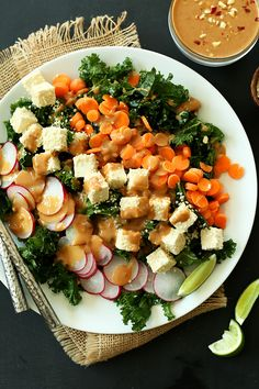 A colorful, crunchy, Thai-inspired salad with kale, carrots, radishes, sesame-tofu, and a spicy-sweet peanut dressing.