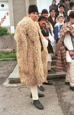 Romanian costume Domneşti - Argeş (Muntenia). Shepherd's cloak called sarică or bituşca, made of several sheepskins worn fleece side out.  The one in the picture has long sleeves which are left hanging (i.e. not used as sleeves). Black căciulă (sheepskin shepherds hat).  Photo was taken in Domneşti, northern Argeş, in May 1999. This village is on the south side of the Carpathians. Similar cloaks are also worn along the north side of the Carpathians.