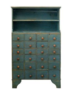 : Blue Apothecary Cupboard Estimate: $2,500 – $4,000  Pine, two shelves on top with molded top, 24 small graduated drawers below with knobs, shaped cutout base with bootjack, horizontal back showing with horizontal planing, T-head nailed construction, 50 1/2″ h, 35 1/2″ w, 12″ d. willis henry