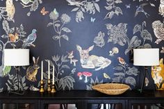 Moody and graphic wallpaper with matching table lamps and small console table with books