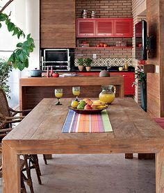 A intenção da designer de interiores Marina Linhares era deixar este espaço com cara de área externa, daí a escolha de materiais rústicos como o cimento queimado e a madeira. Pintados de vermelho, os armários guardam utensílios para churrasco. O lado direito da mesa recebeu banco, em vez de cadeiras